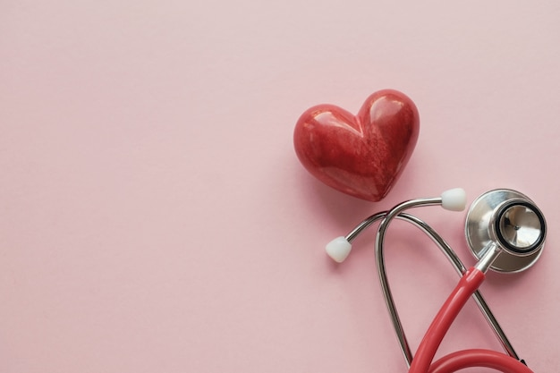 Corazón rojo con estetoscopio sobre fondo rosa Foto Premium