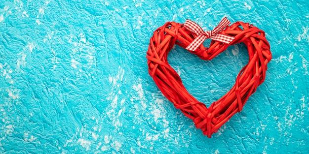 Corazón rojo hecho a mano sobre fondo turquesa, patrón de color aqua con espacio de texto. endecha plana con el concepto de amor, tarjeta de regalo de san valentín, maqueta. diseño de decoración. marco festivo, banner de arte. Foto Premium