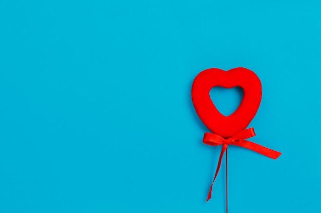 Corazón rojo con un lazo sobre una superficie azul, amor, día de san valentín Foto Premium