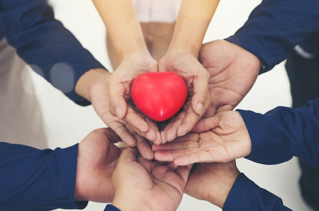 Corazón rojo en las manos juntas colaboran en el trabajo en equipo ...