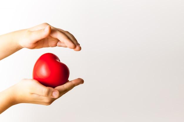 Corazón rojo en manos del niño sobre fondo claro Foto Premium