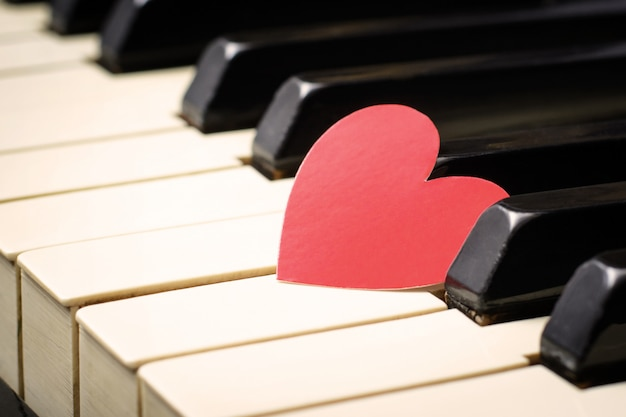 Corazón rojo en las teclas de un teclado de un viejo piano clásico. Foto Premium