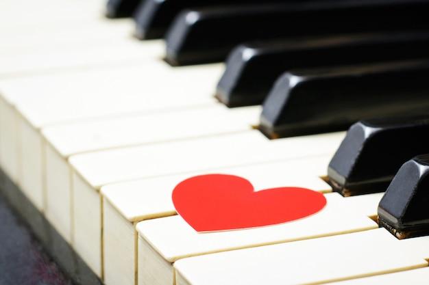 Corazón rojo en las teclas de un teclado de un viejo piano clásico Foto Premium