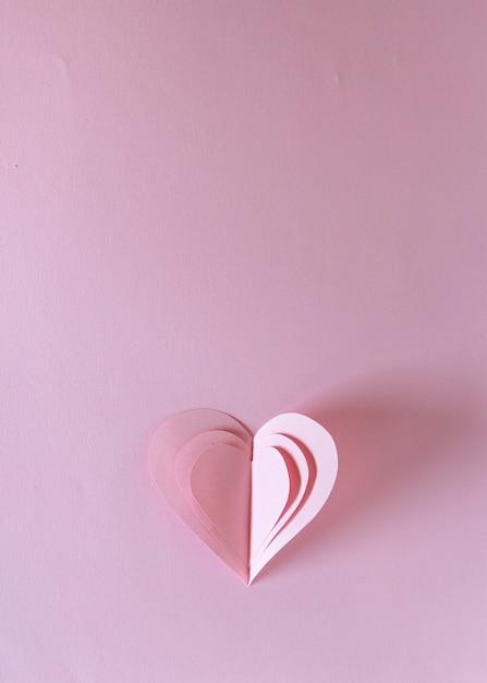 Corazón de san valentín, símbolos únicos de papel del amor en forma de corazón sobre fondo rosa Foto Premium