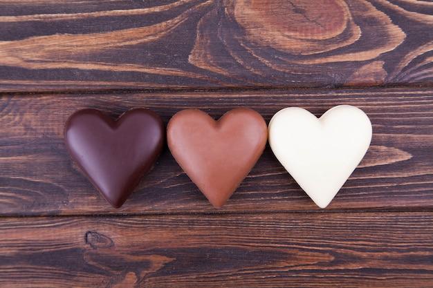Corazones del chocolate en un fondo oscuro, primer. día internacional del chocolate, postal. Foto Premium