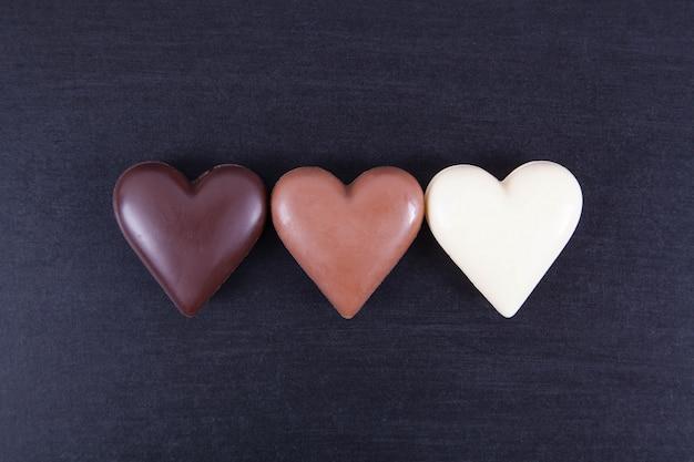 Corazones del chocolate en un fondo oscuro, primer. Foto Premium