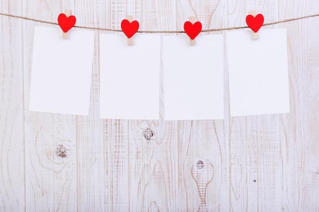 Corazones de fieltro rojo hecho a mano y papel blanco colgado de una cuerda con pinzas para la ropa Foto Premium