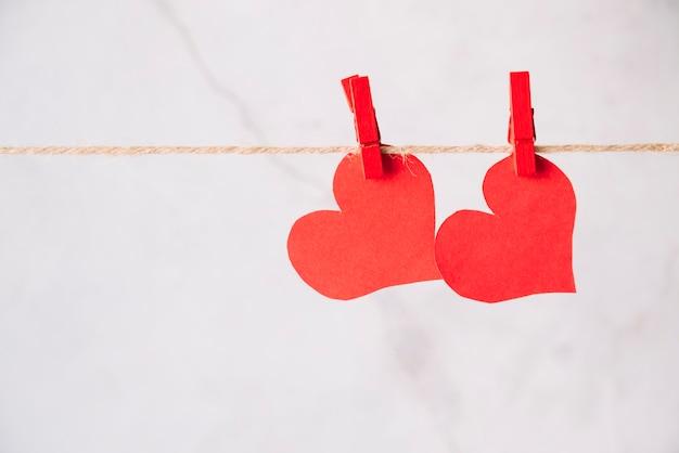 Corazones de papel rojo con alfileres enganchados en hilo. Foto gratis