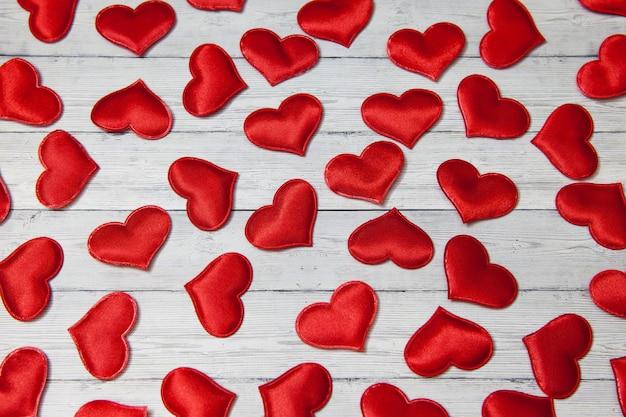 Corazones rojos sobre un fondo de madera, concepto de amor y lealtad. Foto Premium