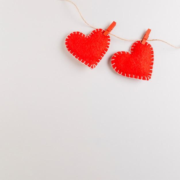 Corazones de tela de fieltro rojo colgando de una cuerda Foto gratis