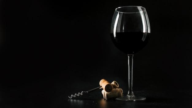 Corchos y sacacorchos cerca de una copa de vino Foto gratis