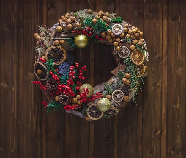 Corona de navidad con bayas de acebo y rodaja de naranja seca colgada en la puerta Foto gratis