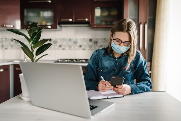 Coronavirus. chica en la máscara de control de aplicaciones sociales en el teléfono. mujer trabaja, aprende y usa la computadora portátil. cuarentena. quédate en casa. persona de libre dedicación. escritura, mecanografía. concepto de comunicación y tecnología. Foto Premium