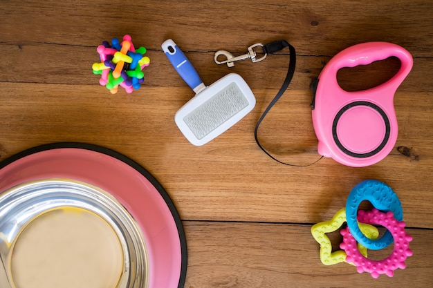 Correas del animal doméstico y juguete de goma en fondo de madera. Foto Premium