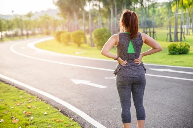 Corredor femenino atleta lesión y dolor de espalda. mujer que sufre de lumbago doloroso mientras se ejecuta en la mañana. Foto Premium