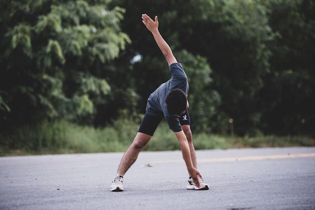 Corredor masculino haciendo ejercicios de estiramiento, preparándose para el entrenamiento Foto gratis