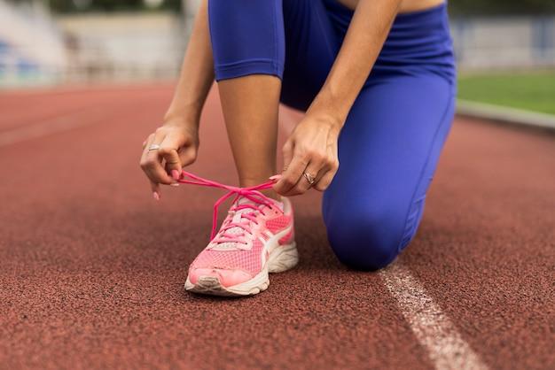 Corredor mujer ata cordones de zapatos Foto gratis