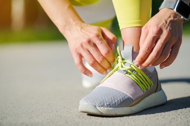 Corredor de mujer atando sus cordones de zapatos preparándose para una carrera matutina Foto Premium