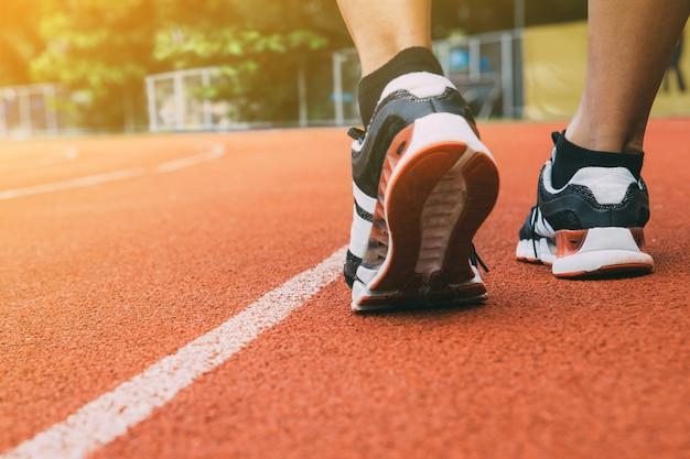 Corredor en una pista con un primer plano de los zapatos. Foto Premium