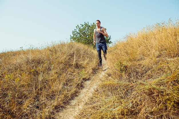 Correr deporte. hombre corredor corriendo al aire libre en la naturaleza escénica. ajuste musculoso atleta masculino sendero de entrenamiento para correr maratón. Foto gratis
