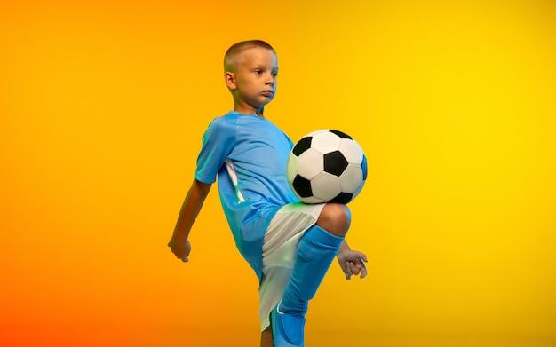 Correr. joven como jugador de fútbol o fútbol en ropa deportiva practicando en estudio amarillo degradado Foto gratis