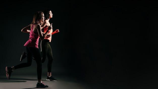 Correr mujeres deportivas en la oscuridad Foto gratis