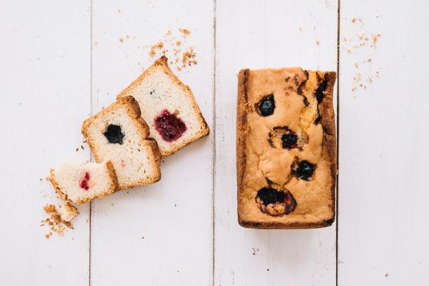 Cortar pastel con mermelada en mesa de madera Foto gratis