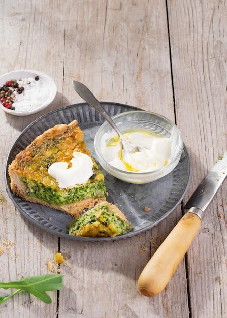 Cortar la quiche en un plato con rúcula, cebolla, espinaca, mozzarella, queso feta y salsa. Foto Premium