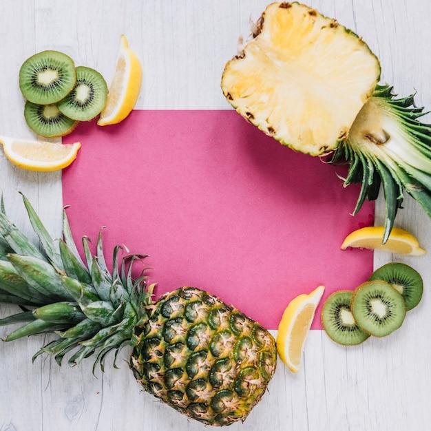 Corte las frutas cerca de la hoja de papel rosa Foto gratis