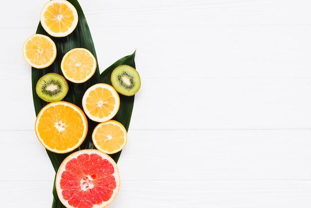 Corte de frutas exóticas frescas en hojas de plátano sobre fondo blanco Foto gratis