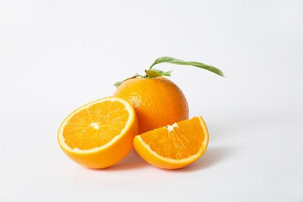 Corte las partes anaranjadas y la fruta entera con hojas verdes. Foto gratis