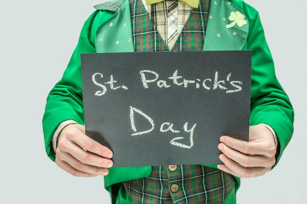 Corte la vista del hombre en traje verde con tableta oscura con palabras escritas el día de san patricio. aislado en gris Foto Premium