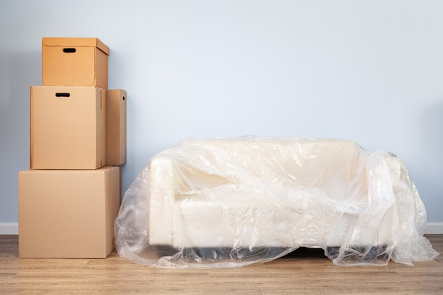 Cosas domésticas empacadas en cajas y sofá empacado para mudarse Foto Premium
