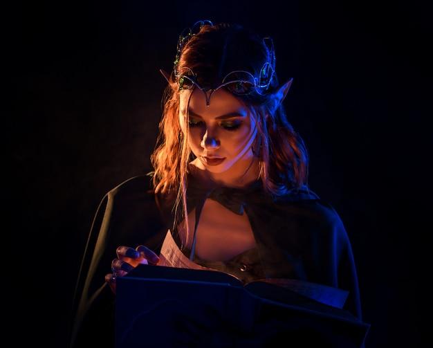 Cosecha del duende encantador joven con el pelo rojo que mira el libro. Foto Premium