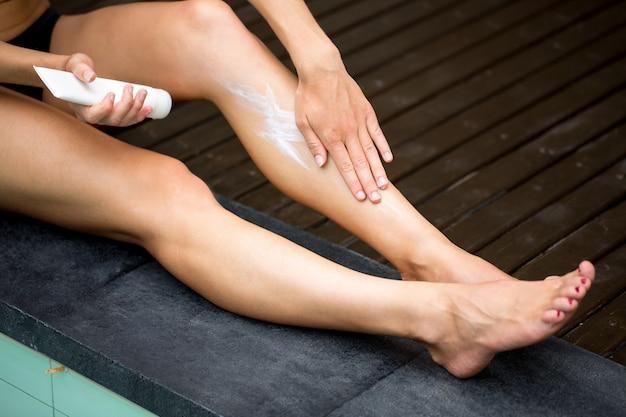 Cosecha, vista, mujer, aplicación, sunblock, piernas Foto gratis