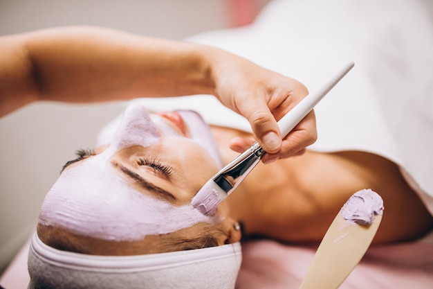 Cosmetóloga aplicando una máscara en la cara del cliente en un salón de belleza Foto gratis