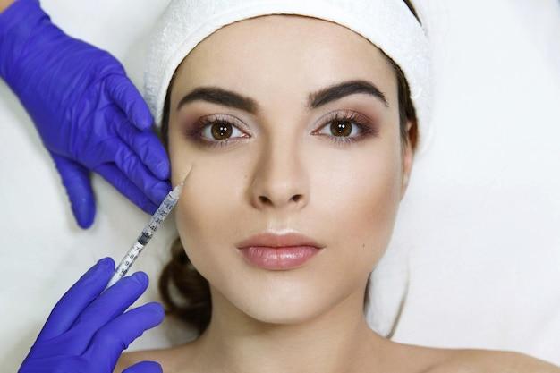 Cosmetóloga hace inyección de belleza en la cara de la mujer en la clínica Foto gratis