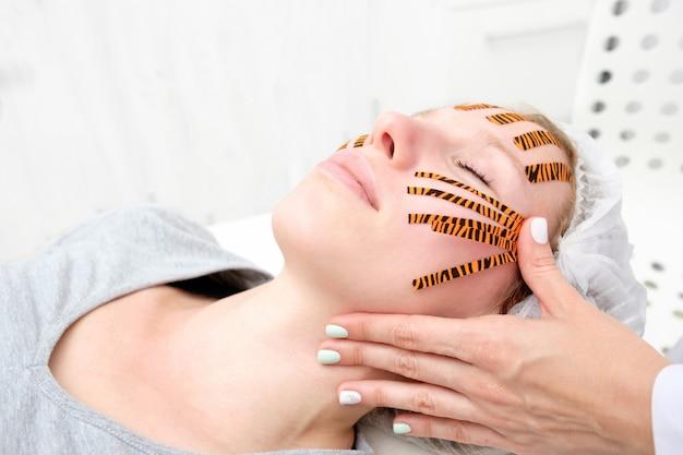 Cosmetóloga haciendo un procedimiento de grabación facial usando cintas de color tigre en un salón de belleza Foto Premium