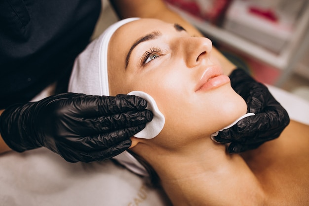 Cosmetóloga limpiando la cara de una mujer en un salón de belleza Foto gratis