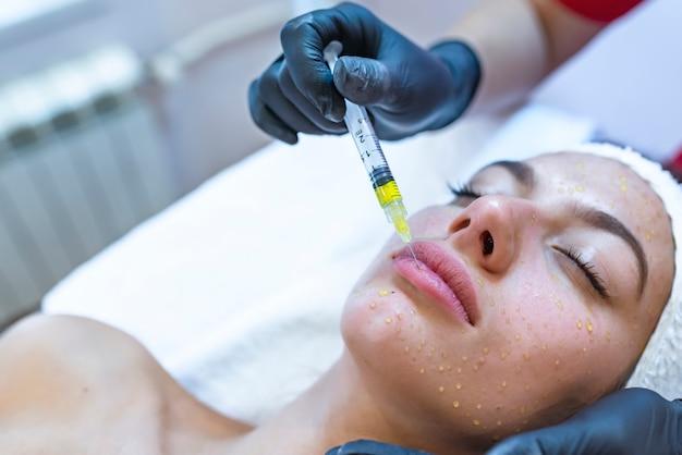 Cosmetología de hardware, mesoterapia, retrato de una mujer joven que recibe tratamiento de la zona de la frente Foto Premium