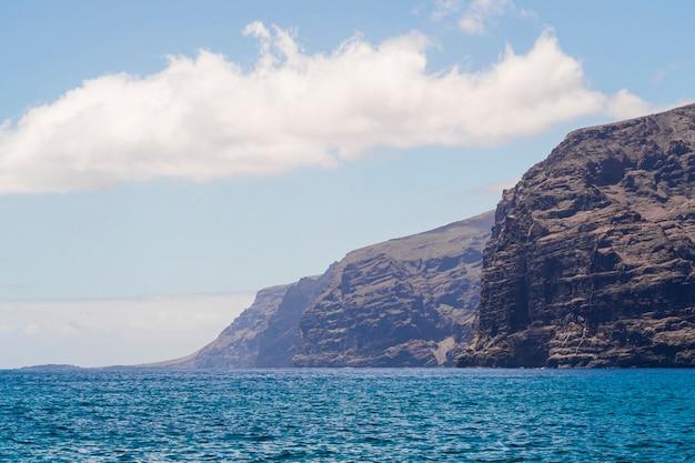 Costa acantilada de tiro largo con agua cristalina. Foto gratis