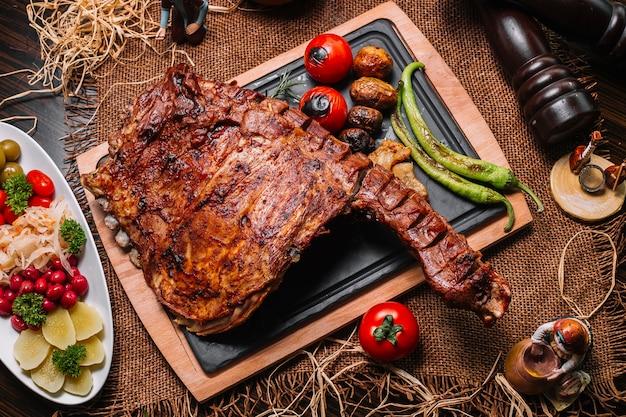 Costillas a la parrilla sobre la plancha de madera tomate pimiento patata vista superior Foto gratis