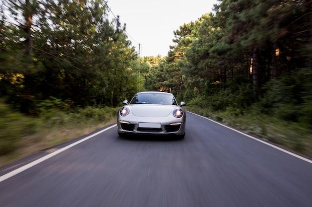 Coupe de color plateado con luces delanteras en la carretera. Foto gratis