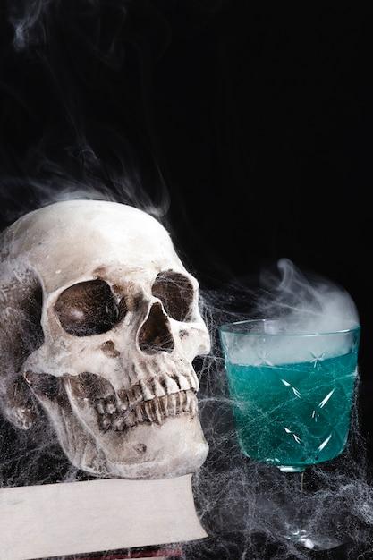 Cráneo humano con bebida verde Foto gratis