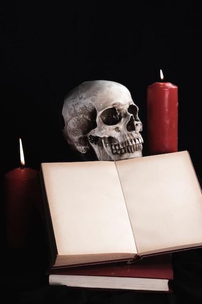 Cráneo humano con maqueta de libro y velas Foto gratis