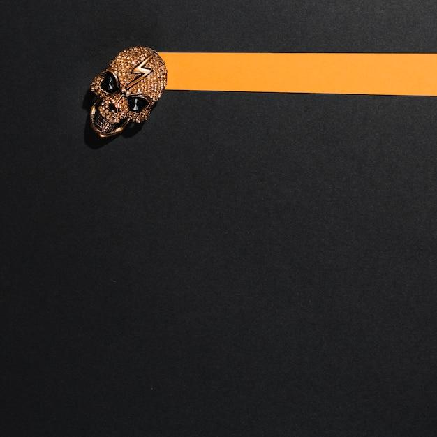 Cráneo de joyas con un rayo en una raya naranja de papel Foto gratis