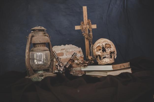 Cráneos en libros con viejas lámparas y pistolas cruzadas Foto gratis