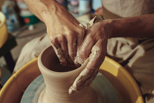 Creando un frasco o jarrón de arcilla blanca de cerca. maestro cántaro. Foto gratis