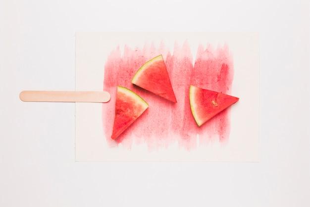 Creativa composición de paletas de sandía madura en palo. Foto gratis