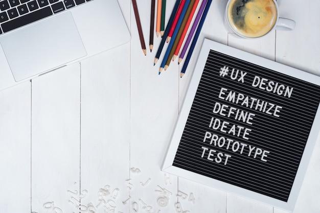 Creativa foto plana del escritorio de trabajo del diseñador ux y el texto del proceso de diseño ux en tablero de fieltro negro. Foto Premium